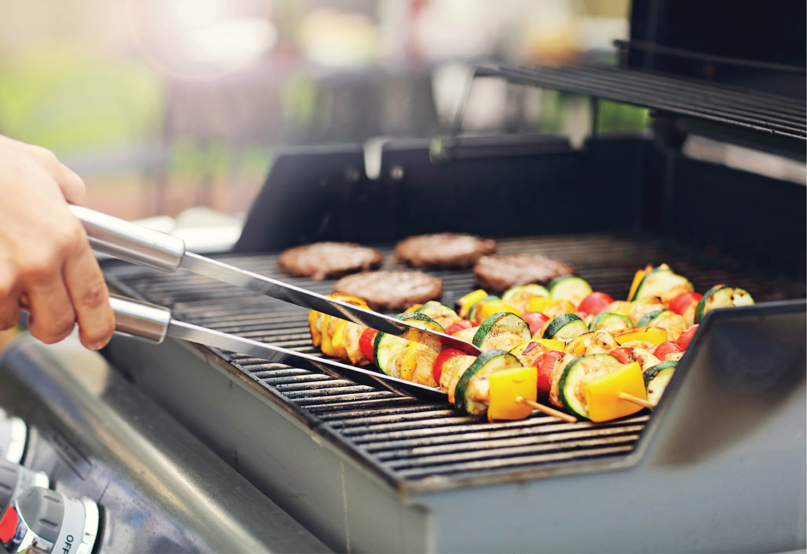Delicious vegetable kebabs with meat patties sizzling on a barbeque grill.