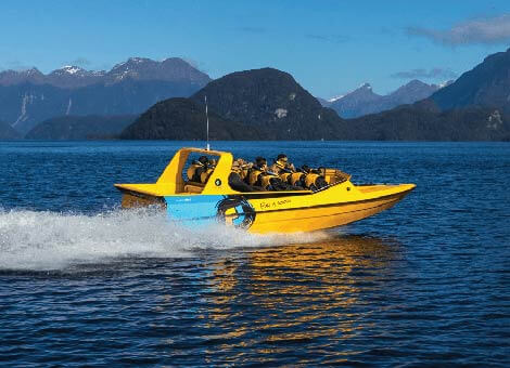 Bright yellow jet boat zooming through the waters of Lake Te Anau with the mountains in the background.