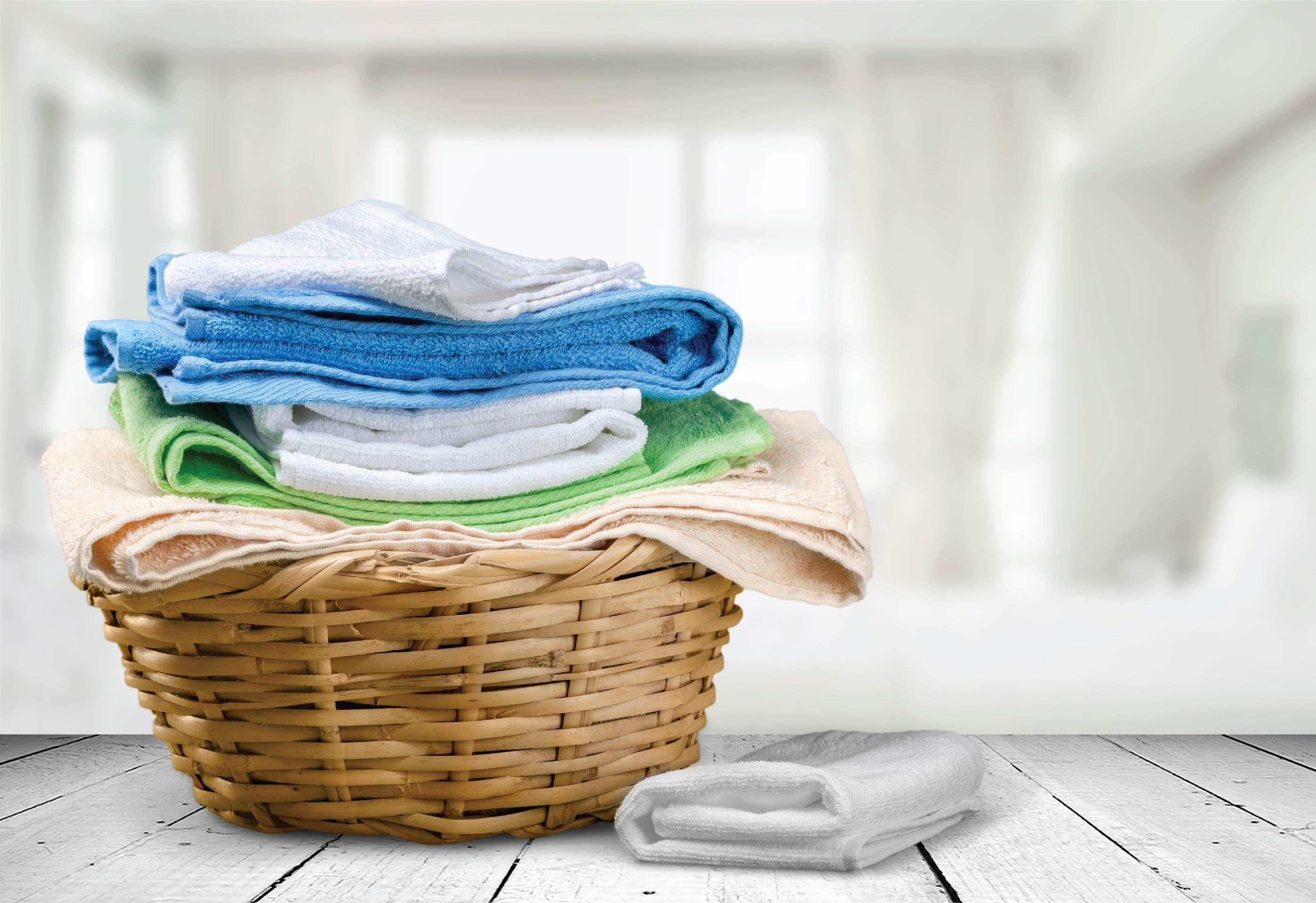 A wooden laundry basket with nicely folded washing piled up.