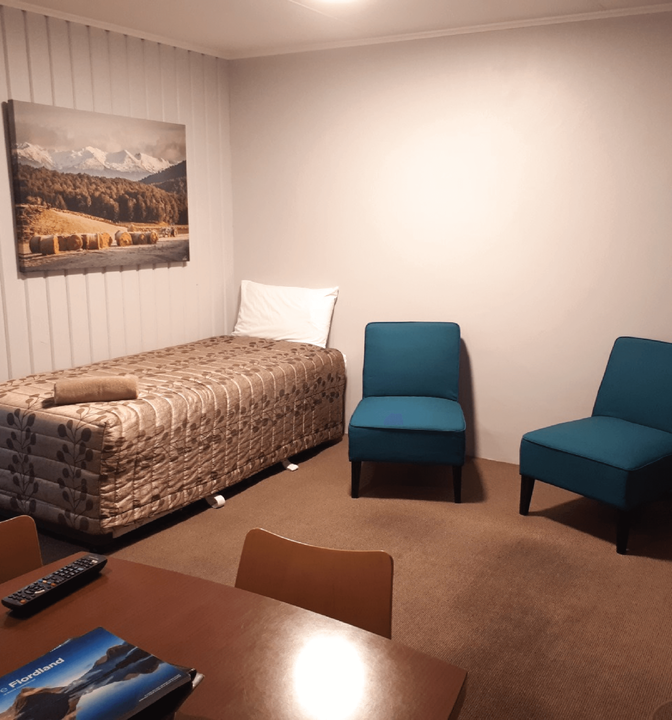 The lounge area of Edgewater Motels standard room. Includes a bed and two seats and table.