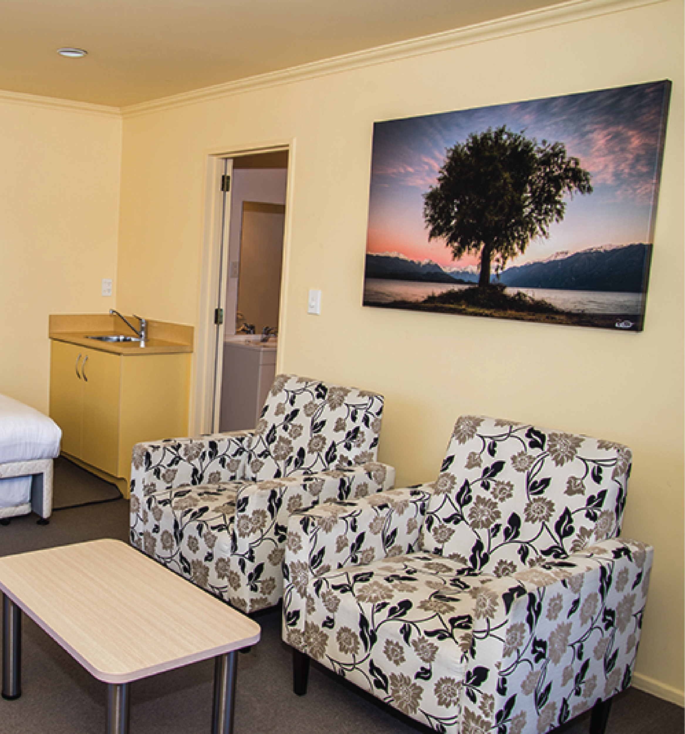 Lounge area of the Edgewater Motel Lakefront unit. Two light-coloured chairs with a large photo of a tree hanging above.