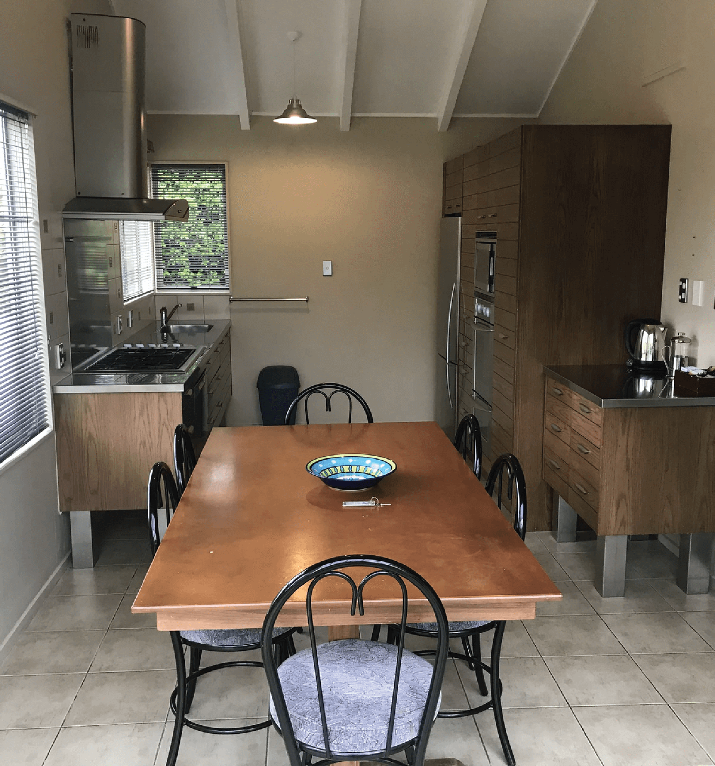 Edgewater Motels Villa kitchen. A modern dark wooden coloured cabinetry with stainless stell benchtop along with a dining table.