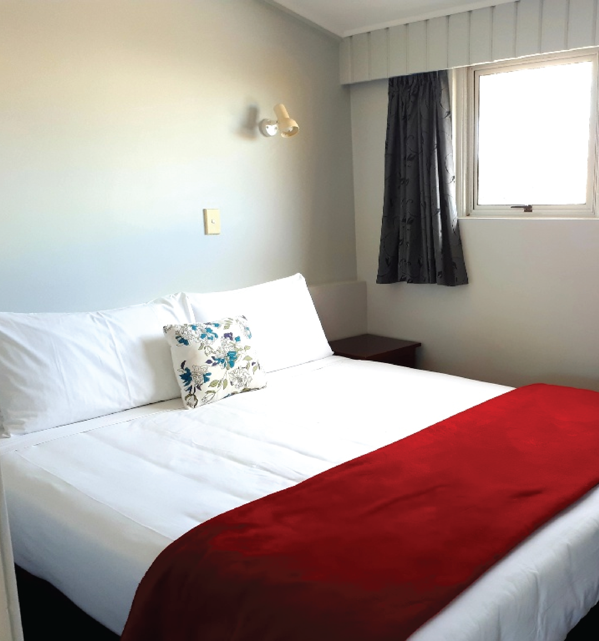 King-sized bed with a red blanket across the end.